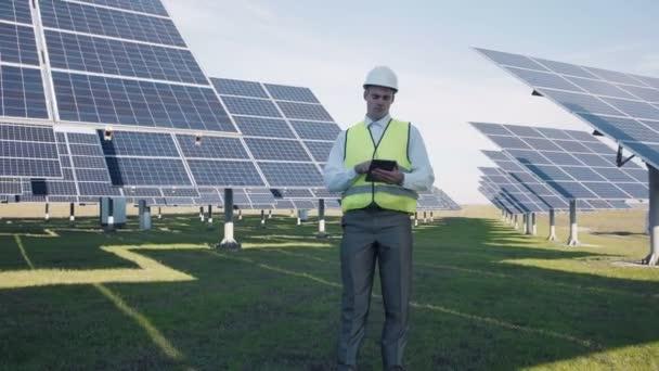 Solární panel technik pomocí tabletu v blízkosti pole