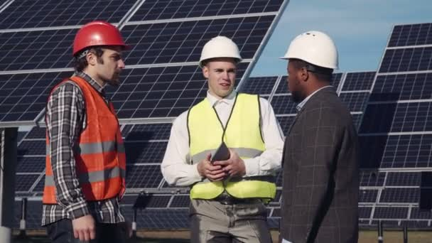 Solar panel workers and manager outside