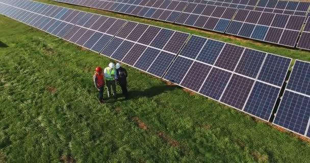 Tři technici na farmě sluneční energie