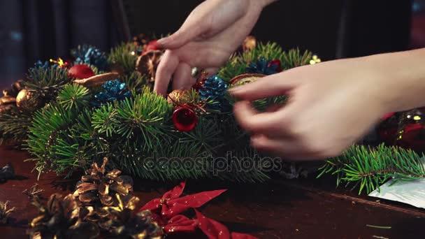 Crop hands decorating Christmas wreath