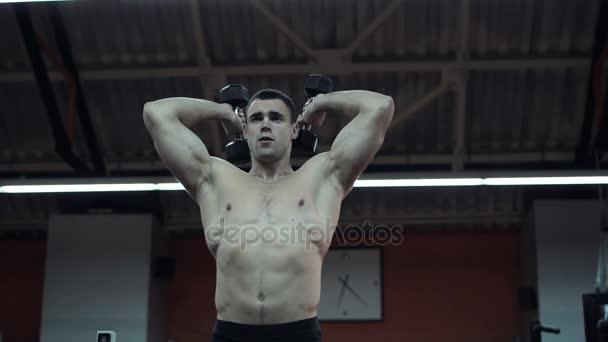 Silné svalové sportovec stojící se vztaženými pažemi