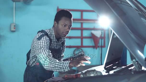 Africké mechanik stojící při pohledu na motor automobilu