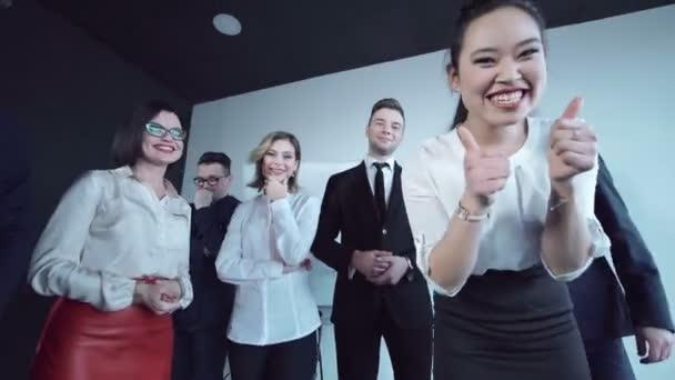 Cheerful team greeting woman