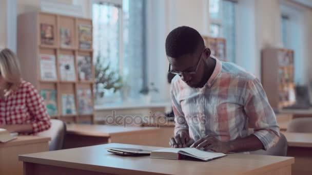 Muž s knihou a tablety v knihovně