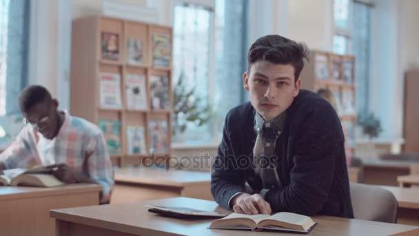 Člověk čte knihu v referenční místnosti