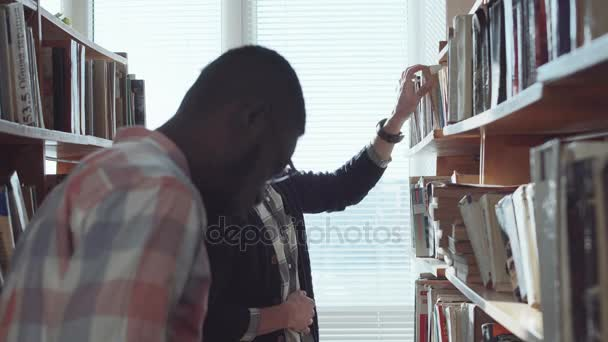 Male students looking for books in library