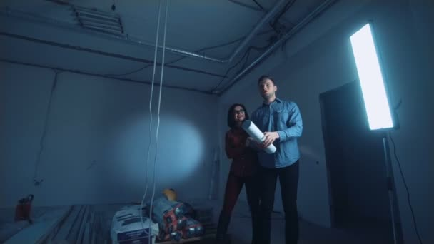 Man and woman looking at blueprint stock video evgeniyshkolenko man and woman looking at blueprint stock video malvernweather Choice Image
