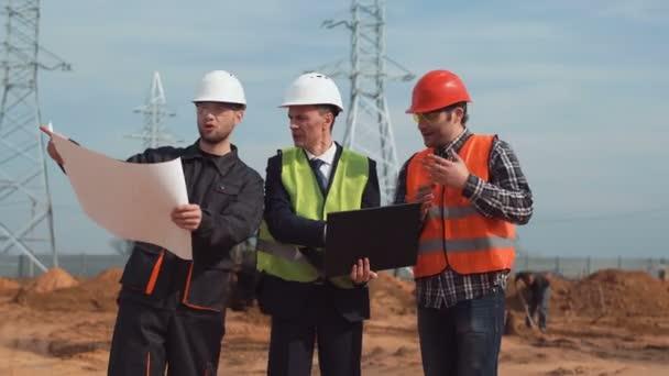 Men on building site discussing the blueprint