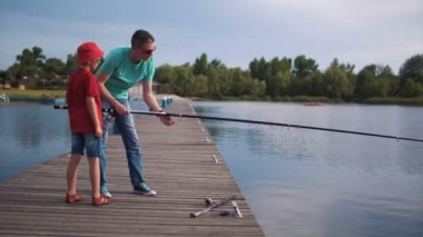 Father and son fishing off a wooden jetty