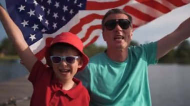 Young boy and his father with the American flag