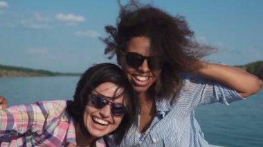 Happy diverse girls in motorboat