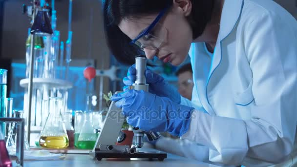 Junge Wissenschaftlerin blickt unter das Mikroskop