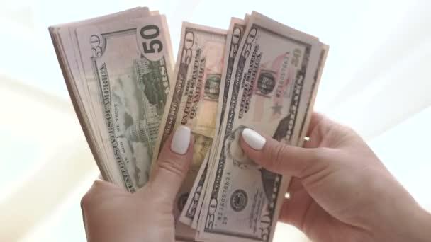 Weibliche Hände beim Zählen von Bargeld.