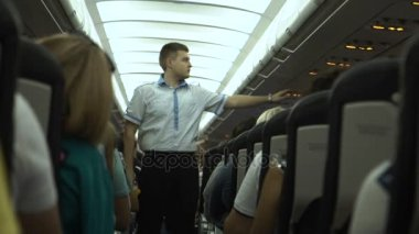 Steward on the plane shows safety rules.