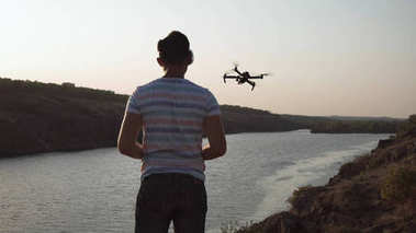 Man controlling drone on river shore