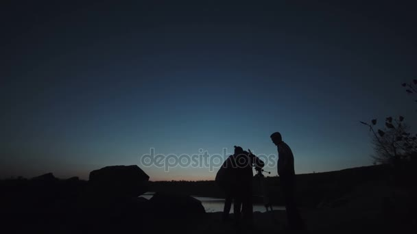 People on shore looking through telescope