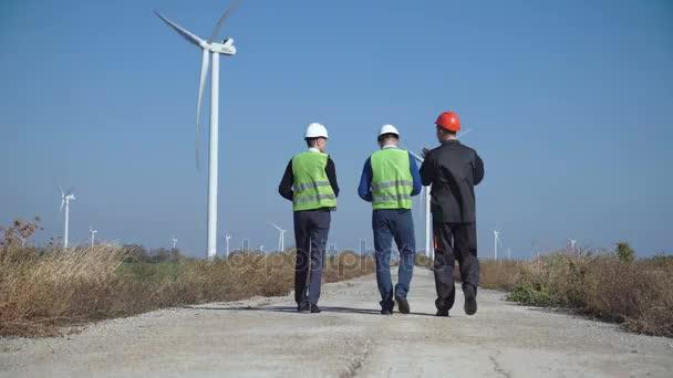 Drei Ingenieure laufen gegen Windpark