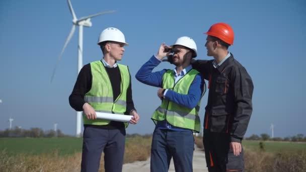 Three engineers discussing against wind turbines