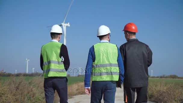 Three engineers walking against wind farm