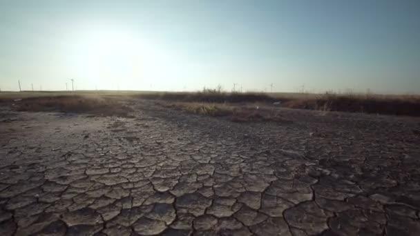 Trockenes Land mit weit entfernten Windmühlen am Horizont