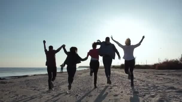 Happy friends running on shoreline