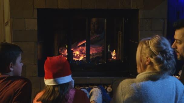 Familie verbringt Weihnachten am Kamin