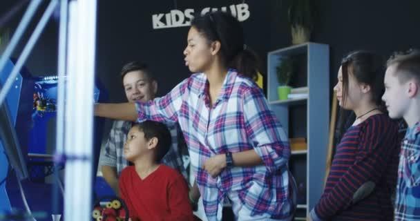 Lehrer zeigt Schüler ein Modell eines Zahnes auf einem dreidimensionalen Drucker gedruckt