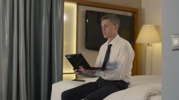 Podnikatel, chatování s přes přenosný počítač v hotelovém pokoji