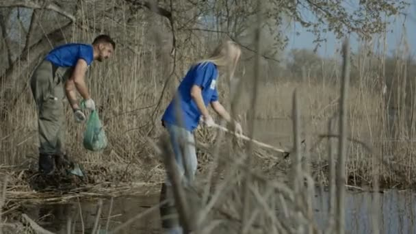 People cleaning pond shore in woods