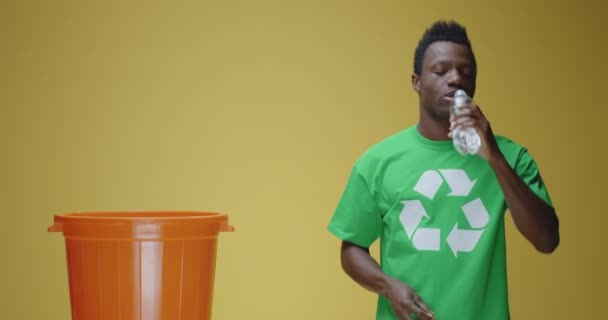 Young man throwing plastic bottle to recycle bin