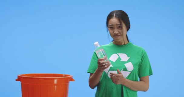 Eco-conscious woman putting bottle into bucket