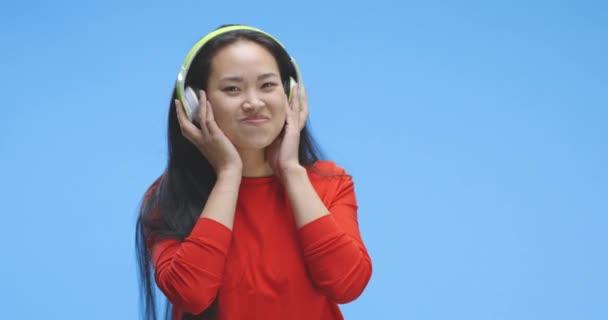 mladá žena poslouchající hudbu na sluchátkách
