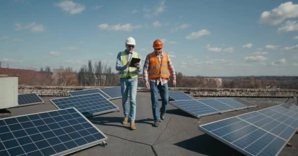 Inženýr a technik diskutující mezi solárními panely