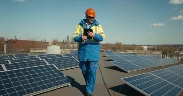 Techniker läuft zwischen Sonnenkollektoren