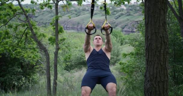 Sportovní muž používající sportovní popruhy