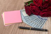 open notebook and pen with rose and dollar