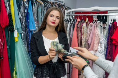 Young woman paying for purchase in dress store