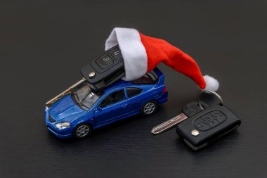 Toy car with santa hat and key on black