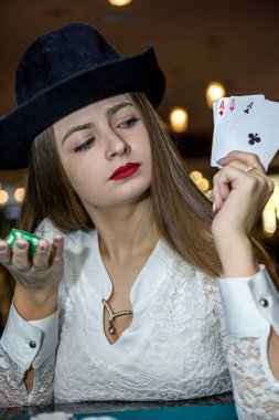 Young lady in casino with four aces