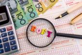 Lupa s australskými dolary a kalkulačkou na daňovém formuláři