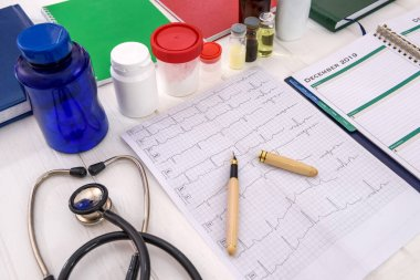 Cardiogram on table with pills in bottles