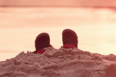Crocs are in the sand on the shore, concept of a summer holiday