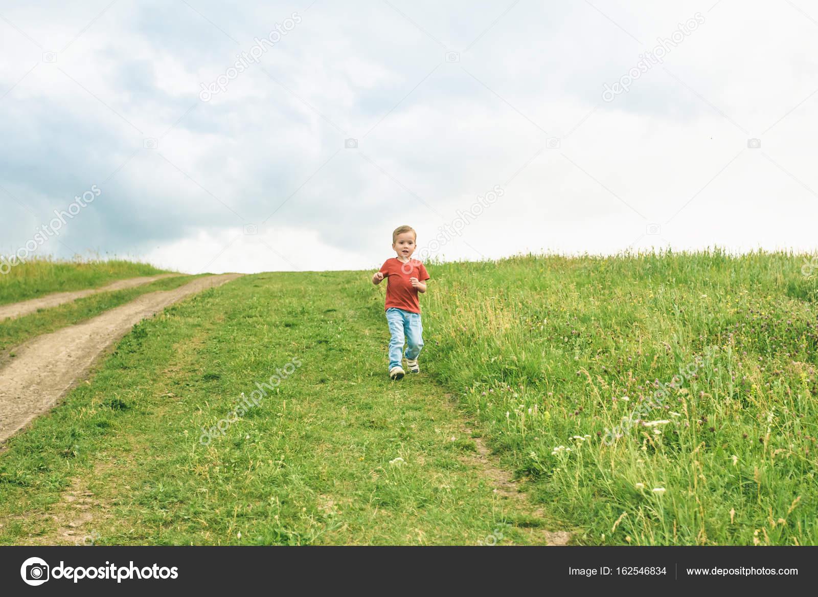Niño Corriendo Por El Campo Sobre El Césped En Un Día
