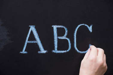 Female hand writing alphabet on black chalkboard. Educational background with ABC letters with copy space