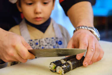Sushi roll making preparation, close-up on chef hands with a knife