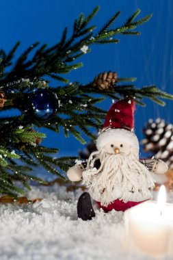 Toy Santa Claus is sitting under a Christmas tree.
