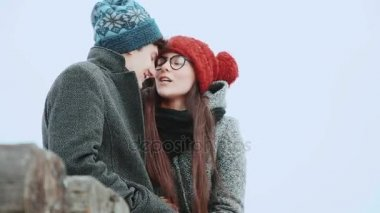 Woman with a young man in a coat and knit cap, sitting, against the gray sky, they are talking laughing.