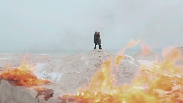 Pár stojící na pozadí ohně, na kopci písku. Zimní moře