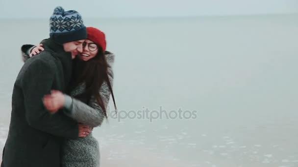 junges Paar im grauen Wintermantel, küsst sich gegen den grauen Himmel und das Meer.