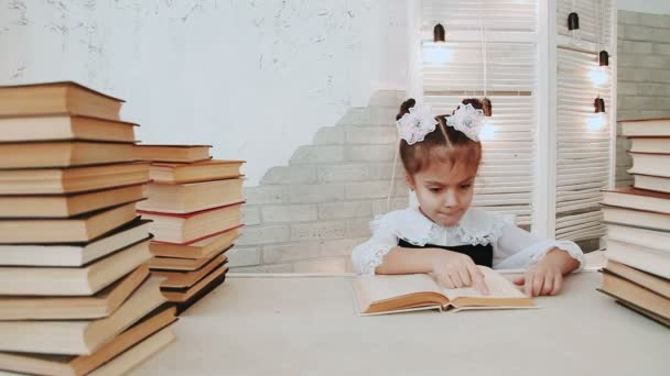 Schoolgirl sitting at a table and reading a book.